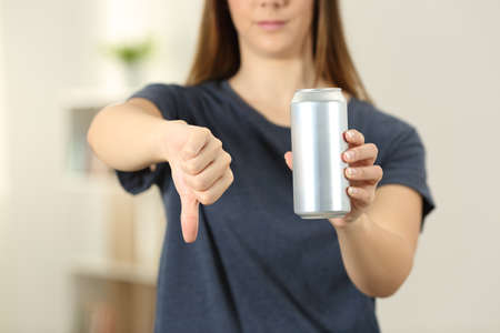 Photo pour Front view close up of a woman hands holding a soda drink can with thumbs down at home - image libre de droit