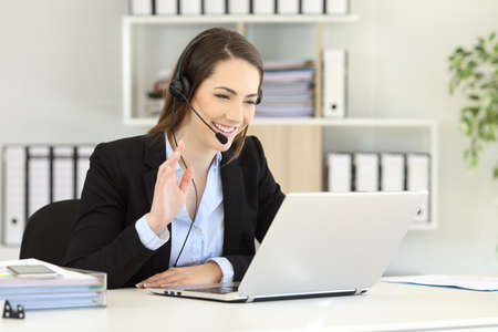 Photo for Happy telemarketer having a video conference with a laptop waving with her hand at office - Royalty Free Image