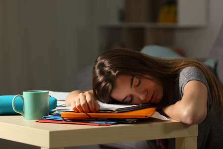 Photo pour Exhausted student sleeping over homework late night at home - image libre de droit