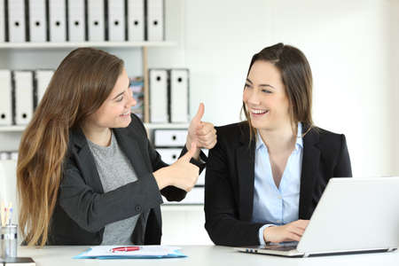 Photo for Office worker congratulating her colleague for a good job - Royalty Free Image