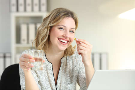 Photo pour Happy office worker showing a vitamin supplement pill and a water glass looking at camera - image libre de droit