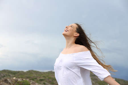 Foto de Positive woman breathing fresh air enjoying the wind - Imagen libre de derechos