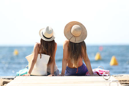 Foto de Back view of two tourists looking at horizon over the sea on summer vacations relaxing on the beach - Imagen libre de derechos