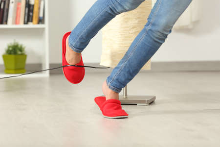 Photo pour Close up of a woman legs stumbling with an electrical cord at home - image libre de droit