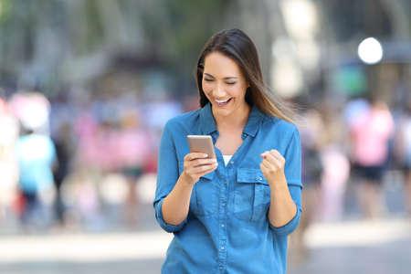 Foto de Front view of a excited woman reading good news in a smart phone online on the street - Imagen libre de derechos