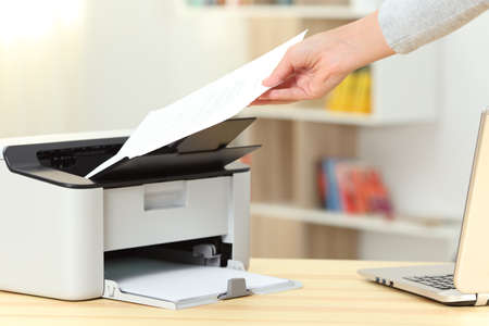 Photo pour Close up of a woman hand catching a document from a printer on a desk at home - image libre de droit