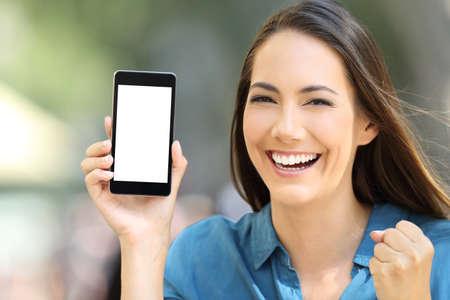 Foto de Excited woman showing a blank phone screen mock up on the street - Imagen libre de derechos