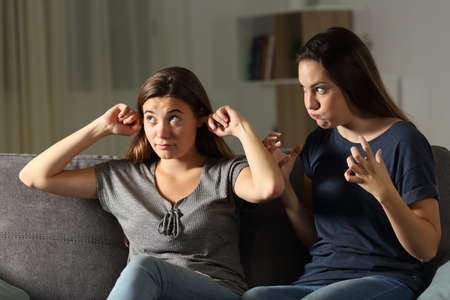 Foto de Furious woman and friend ignoring her sitting on a couch in the living room at home - Imagen libre de derechos
