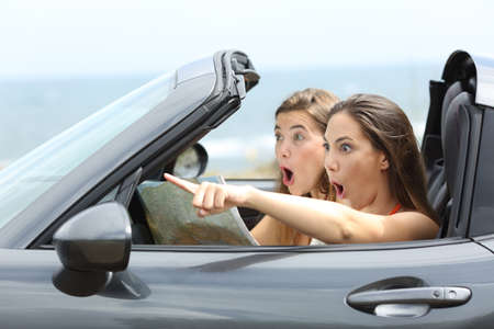 Photo pour Amazed girls in a car pointing away on summer vacations - image libre de droit
