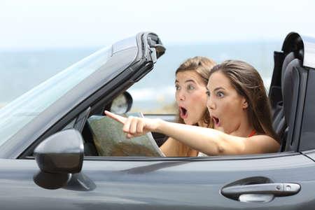 Foto de Amazed girls in a car pointing away on summer vacations - Imagen libre de derechos