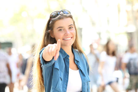Photo for Single happy woman pointing and looking at camera standing in the street - Royalty Free Image