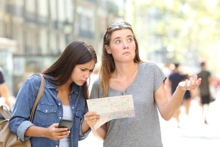 Foto de Two lost tourists consulting a paper map and a smart phone searching location in the street - Imagen libre de derechos