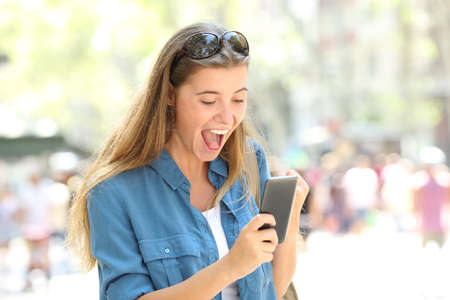 Foto de Excited girl reading good news holding a smart phone in the street - Imagen libre de derechos