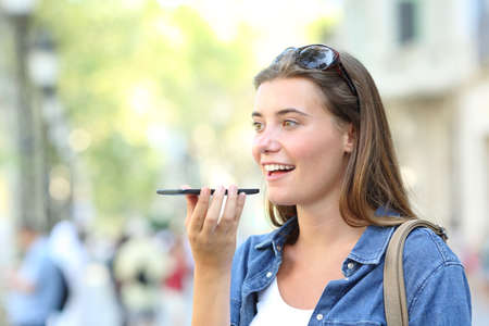 Photo pour Happy girl using voice recognition of the smart phone in the street - image libre de droit