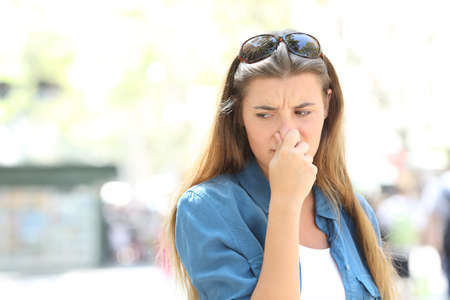 Photo pour Girl covering nose in the middle of a contaminated city street - image libre de droit