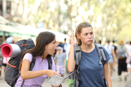 Photo pour Angry backpackers arguing during vacation travel in a big city street - image libre de droit
