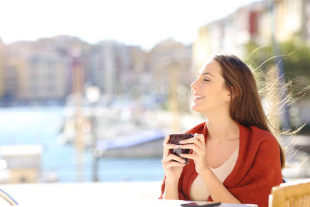 Photo pour Side view portrait of a happy woman breathing fresh air in a coffee shop on vacation on the beach - image libre de droit