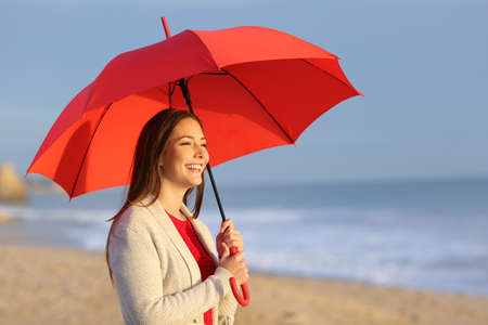 Foto de Happy girl with red umbrella watching sunset or sunrise on the beach - Imagen libre de derechos