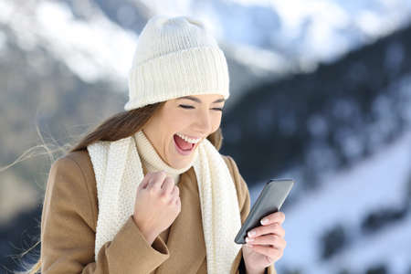 Foto de Excited girl checking online news in winter in a snowy mountain - Imagen libre de derechos