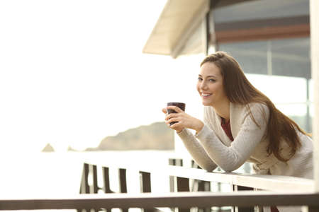 Photo pour Happy hotel guest holding a coffee cup looking at you from a balcony on vacation - image libre de droit