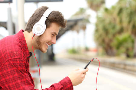 Photo pour Side view portrait of a happy man listening to music with phone and headphones waiting in a train station - image libre de droit