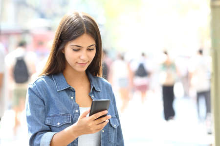 Photo pour Beautiful relaxed teen using a smart phone walking in the street - image libre de droit