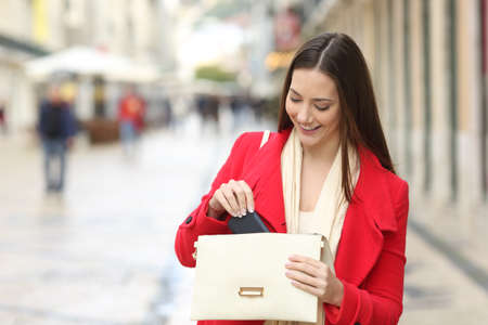 Photo for Happy woman in red taking out the phone from the bag in the street in winter - Royalty Free Image