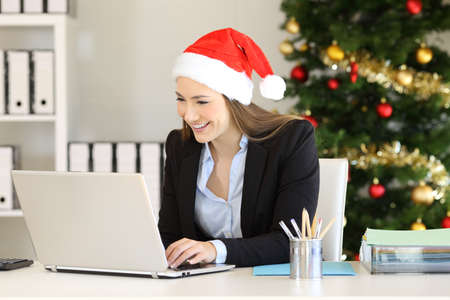 Photo for Happy office worker working with a laptop in christmas time - Royalty Free Image