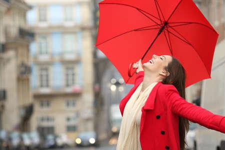 Photo pour Spontaneous woman holding a red umbrella celebrating success under the rain in winter - image libre de droit