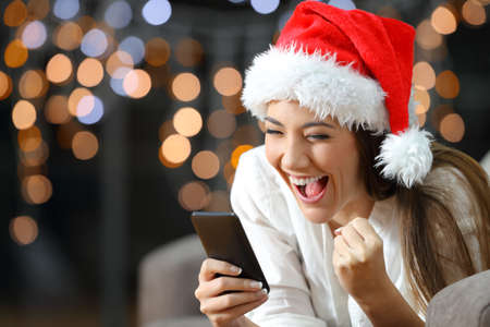 Foto de Excited woman reading text on a phone on christmas lying on a couch in the living room at home - Imagen libre de derechos