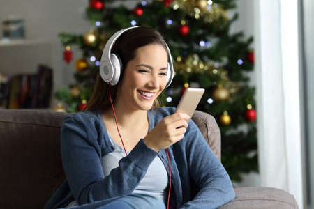 Photo pour Happy girl wearing headphones listening to music in christmas sitting on a couch in the living room at home - image libre de droit