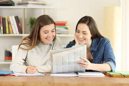 Foto de Two happy students talking about newspaper news at home - Imagen libre de derechos