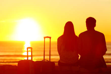 Photo pour Back view backlight silhouette of a couple of travelers looking at sun on vacation travel - image libre de droit