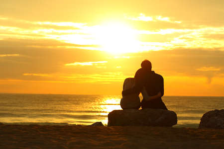 Photo pour Backview backlight of a couple silhouette dating at sunset on the beach - image libre de droit