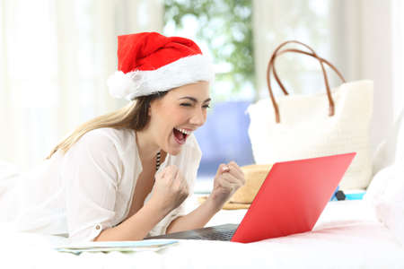 Foto de Excited woman with a laptop on christmas holidays lying on a bed in an hotel room - Imagen libre de derechos