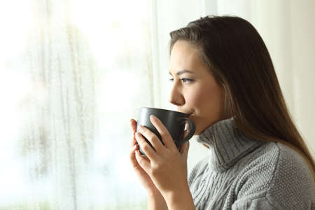 Photo pour Happy woman drinking coffee looking at rain through a window at home or hotel in winter - image libre de droit