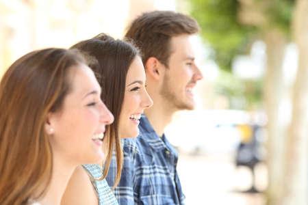 Foto de Profile of three happy friends looking away in the street - Imagen libre de derechos