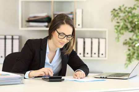 Photo for Office worker wearing eyeglasses doing accounting on a desk - Royalty Free Image