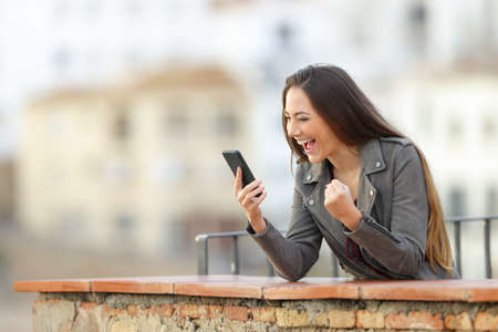 Foto de Excited woman checking smart phone in a balcony with a town in the background - Imagen libre de derechos