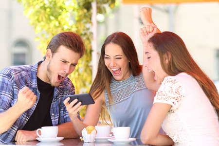 Foto de Three excited friends celebrating good news watching smart phone media content in a coffee shop - Imagen libre de derechos