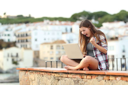Foto de Excited teenage girl checking laptop content sitting on a ledge in a coast town on vacation - Imagen libre de derechos