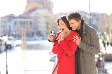 Photo pour Happy boyfriend asking marry to his glad girlfriend in a coast town in winter - image libre de droit