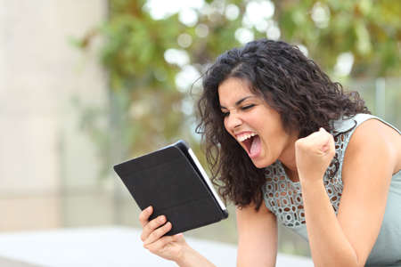 Foto de Excited girl holding a tablet and celebrating news on line in a park - Imagen libre de derechos