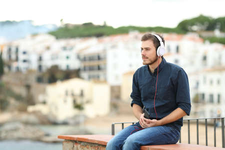 Photo pour Serious man listening to music from smart phone sititng on a ledge on vacation - image libre de droit