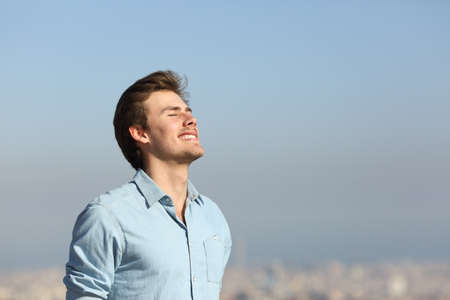 Photo pour Happy man breathing deeply fresh air in the city outskirts - image libre de droit