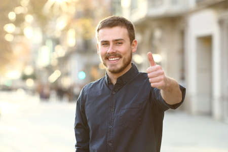Photo for Front view portrait of a happy man in the street gesturing thumbs up - Royalty Free Image