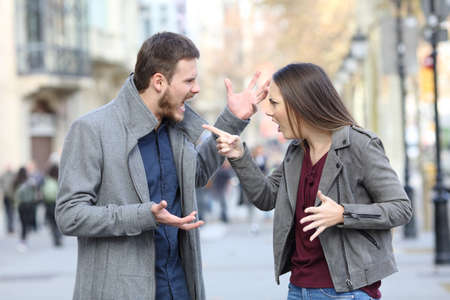 Photo pour Angry couple arguing in the middle of a city street - image libre de droit
