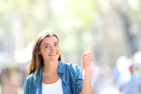 Foto de Front view portrait of a happy girl pointing at side in the street looking at you a sunny day - Imagen libre de derechos