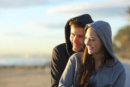 Photo pour Happy couple of teens contemplating sunset siting on the beach - image libre de droit