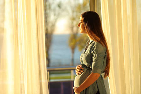 Photo pour Side view portrait of a serious pregnant woman looking through a window at sunset - image libre de droit
